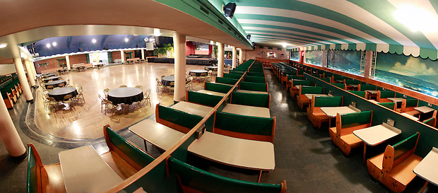 1/19/12 1:06:41 PM -- Clear Lake, IA, U.S.A. -- THIS IS FOR A LIFE COVER:.A 180 degree view of the Surf Ballroom as seen from the ballroom's booths in a panoramic composite from six photographs..On Feb. 3, 1959, Buddy Holly, Ritchie Valens and the Big Bopper died when their plane crashed in a farm field north of Clear Lake, Iowa ? an event memorialized as ?the day the music died? in the 1971 song American Pie by Don McLean. The three 1950s stars played their last gigs at Clear Lake?s Surf Ballroom, which is intact today and holds an annual celebration of its moment in music history. The ballroom, largely the same as it was in its ?50s heyday, struggled as a for-profit business and has been operated as a non-profit since 2008. It hosts concerts, weddings, reunions and school tours. It has a small museum, but the big draw is the place itself. The maple dance floor and booths are original. One of the two original coat checks is still there and so is the phone that Holly used to call his wife before the fatal crash, the website boasts. The fun part is the annual gathering of fans from all over the world, which this year is Feb. 1-4 and is delicately called the ?winter dance party.? There are concerts each night, a bus outing to the crash site, which is marked by a giant pair of the glasses Holly wore, dance lessons, video and art contests and a gathering of the British Buddy Holly Society (whose members have been coming to Clear Lake for 23 years). Chuck Berry is a featured performer this year. It?s a charming and weird slice of Iowa life and rock ?n? roll history. -- ...Photo by Christopher Gannon for USA TODAY.
