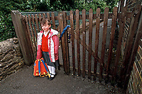 Little schoolgirl left standing outside the locked school gates waiting for her parents to pick her up and take her home. All the rest of the children have gone and she is all alone.This image may only be used to portray the subject in a positive manner..©shoutpictures.com..john@shoutpictures.com