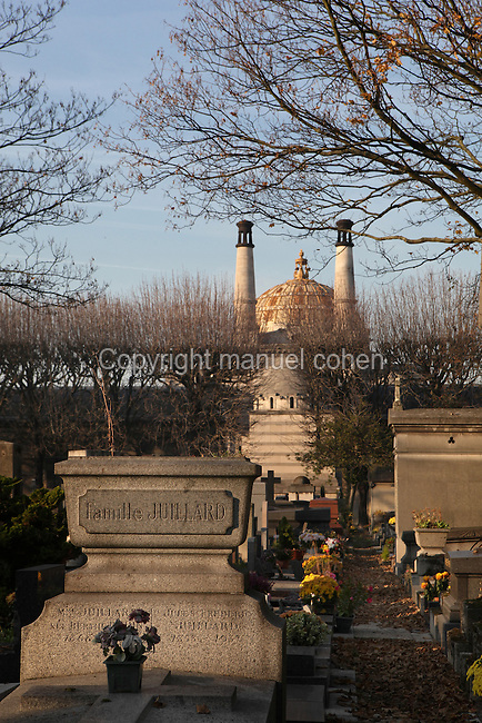 Funerary monument to Famille Juillard with the dome and chimneys of Neo-Byzantine style Crematorium, 1908, Camille Formige, in the background, Pere Lachaise Cemetery (Cimetiere du Pere-Lachaise), Paris, France, opened 1804, designed by Alexandre-Theodore Brongniart. Named after Pere Francois de la Chaise (1624-1709), confessor to Louis XIV (1638-1713), who lived in the Jesuit house on the site of the chapel. Picture by Manuel Cohen