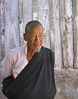 An wise-looking, older man in traditional dress with a thoughful look, all-knowing look on his face as he walks past a sun-bleached wooden structure in Wangdue Phodrang, Bhutan.