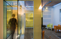 The inner courtyard is visible through the glass panels and was built with natural materials