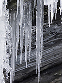 Switzerland. Icicles hanging from a rock; frozen waterfall forms an icy cascade.