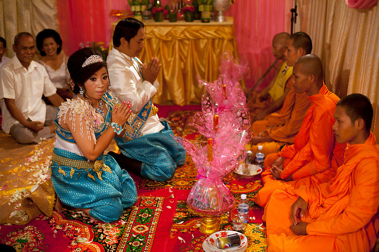 Bride and groom pray to Buddhist monks at a buddhist wedding in a small village outside of Phnom Penh, Cambodia. <br /> <br /> Photos &copy; Dennis Drenner 2013.