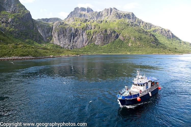 Small tourist boat in mountainous fiord landscape, Raftsundet strait, Nordland, northern Norway