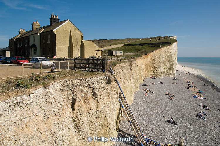 Surviving cottages in a terrace partly lost to coastal erosion of the chalk cliffs in the village of Birling Gap, East Sussex.