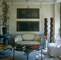 A small Louis XVI sofa stands on the black and white marble floor of the main reception room flanked by an eclectic collection of furniture and artefacts