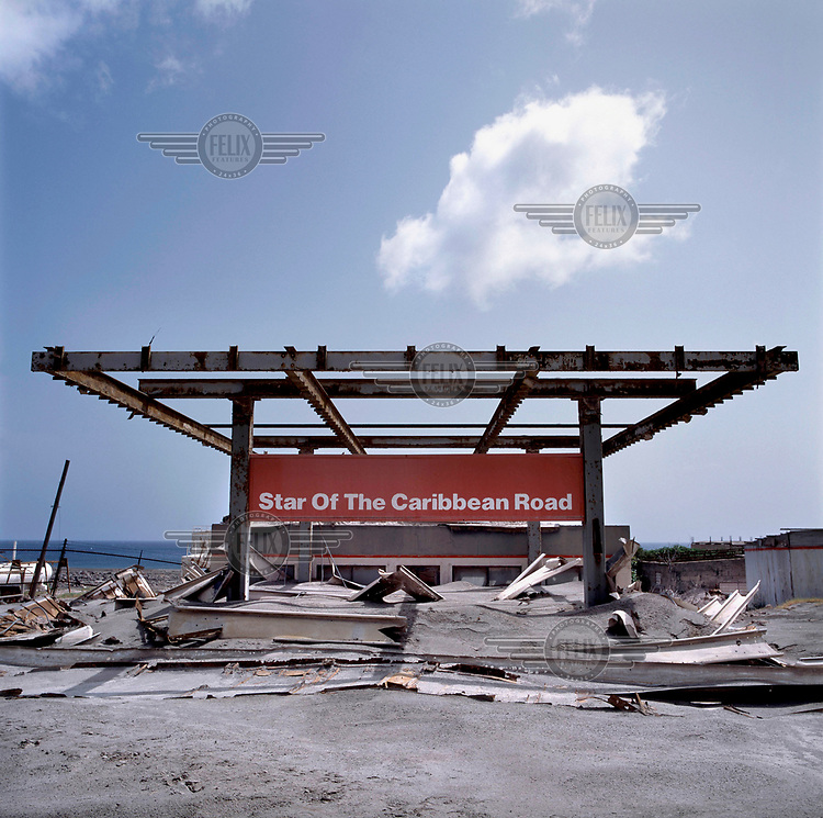 The steel frame of the Star of The Caribbean petrol station protrudes from a layer of ash, mud and rock from the pyroclastic flow which descended on the former capital during the Soufriere Hills volcanic eruption. <br /> <br /> The volcano began erupting in July 1995, and remained active through the subsequent decade. Up to 7,000 of the 10,500 inhabitants have been evacuated from the island, while other residents have been moved to the northernmost areas. The southern region affected by the eruption is designated out of bounds to everyone except scientists.