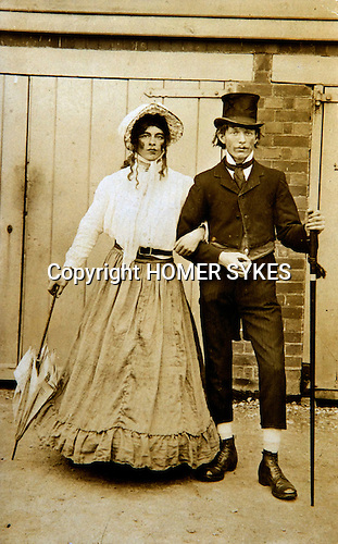 """Cross dressing man,  couple dressed as woman of higher social status with her husband dressed in top hats and tail coat. Photo taken circa 1900 probably ay a village fair  or fete. A real photo postcard probably only one copy printed. 1900s. Never sent on the reverse its jusr read """"Dolly""""."""