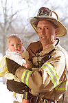 fireman holding and protecting infant baby at scene of house fire, emergency, rescue