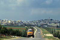 Truck driving on road, leaving Madaba, Jordan.