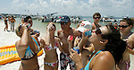 Amanda Giunipero (R), from Tallahassee, Florida, and her friends drink shots of tequila on the beach at the 2006 White Trash Bash on Dog Island May 28, 2006, off the coast of Carrabelle, FL.  The White Trash Bash is a yearly boat party on remote Dog Island, 75 miles south of Tallahassee, Florida,  This year's party drew thousands of participants that arrived in over 350 boats.    (Mark Wallheiser/TallahasseeStock.com)