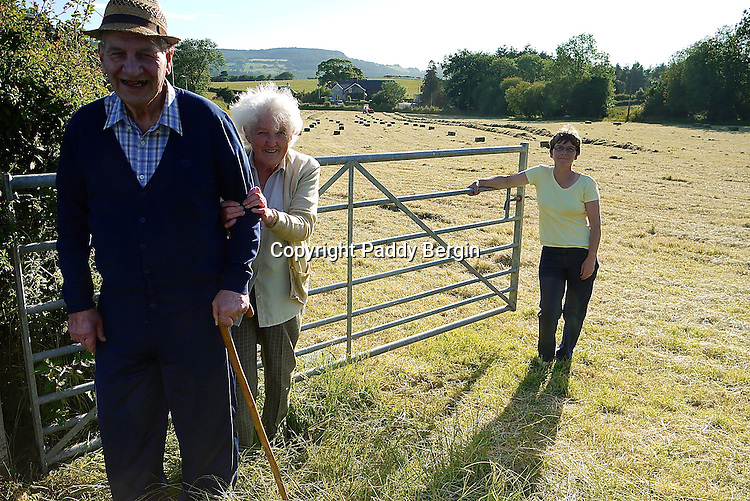 The farmer and his wife on a small family owned farm in the village of Llanafan which is in the county of Ceredigion, West Wales. The village is situated on the north side of the beautiful Ystwyth Valley and the river eventually flows into the sea at the seaside town of Aberystwyth. Haymaking for this farm is an important time and is dependant on the weather. When its good enough and the grass is cut it is left to dry and then collected as in these photos. Local people come and help to ensure all the hay is brought in and stored in the barn.<br />