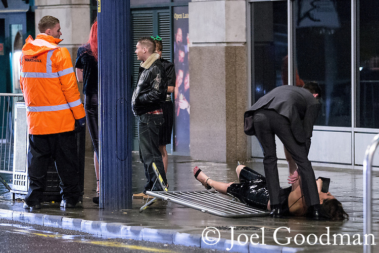 © Joel Goodman - 07973 332324 . 21/12/2013 . Manchester , UK . A woman falls over a barrier in a taxi queue . Christmas revellers out in the rain in Manchester on Mad Friday , the last Friday night before Christmas which is typically one of the busiest nights of the year for police and ambulance crews . Photo credit : Joel Goodman