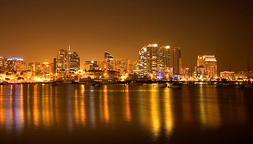 THE BRIGHT LIGHTS OF DOWNTOWN SAN DIEGO, CALIFORNIA, LIGHT UP THE HARBOR AREA UNDER A FULL MOON