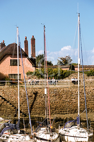 Porlock Weir, Somerset, England. Pink painted thatched holiday cottage overlooking the harbour with yachts.