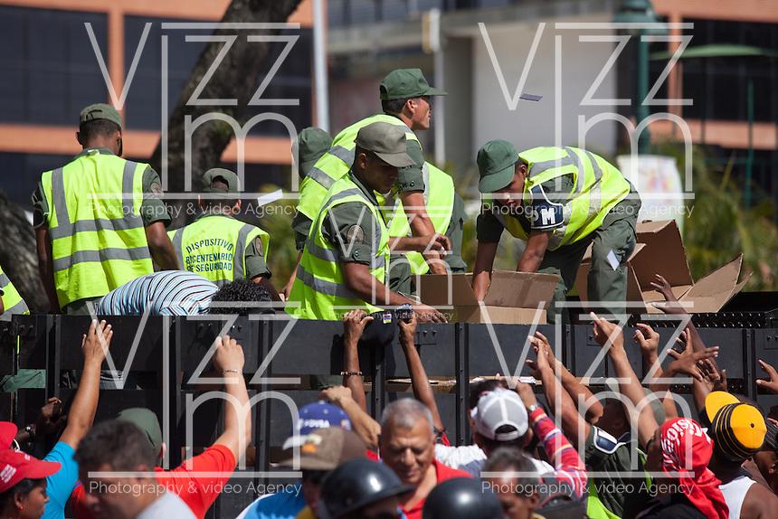 CARACAS - VENEZUELA 08-03-2013, Policías reparten comida y agua hoy durante el funeral de estado de Chávez. El lider y  presidente de Venezuela, Hugo Chávez Frías, falleció el pasado martes 5 de marzo de 2013 a causa de un cancer a la edad de 58 años./ Police officers give to people food and water today during the state funeral of Chavez. The leader and president of Venezuela, Hugo Chavez Frias who died by cancer the past March 5th of 2013 at the age of 58. Photo: VizzorImage / CONT