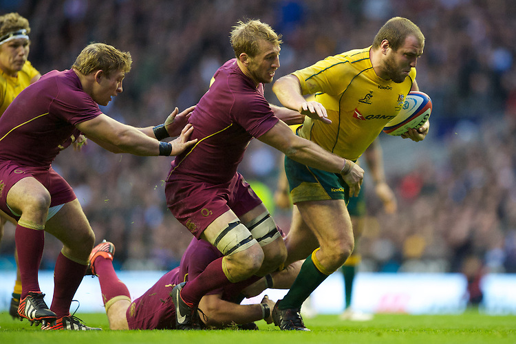 Ben Alexander of Australia forces his way through the tackle of Chris Robshaw of England during the Cook Cup between England and Australia, part of the QBE International series, at Twickenham on Saturday 17th November 2012 (Photo by Rob Munro)
