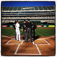 OAKLAND, CA - AUGUST 24: Instagram of coach Chip Hale of the Oakland Athletics talking to umpires at home plate before the game against the Los Angeles Angels at O.co Coliseum on August 24, 2014 in Oakland, California. Photo by Brad Mangin