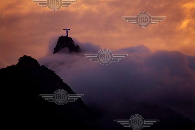 Clouds billow beneath the statue of Christ the Redeemer on Corcovado mountain in the Tijuca Forest National Park.