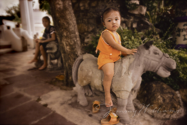 A little girl from Thailand sits on a stone horse statue outside of her home.