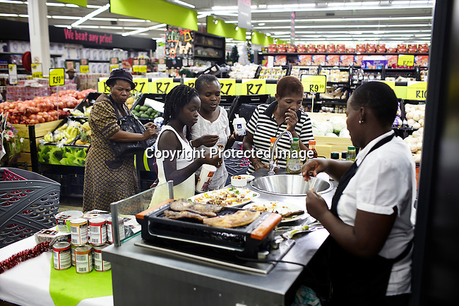 SOWETO, SOUTH AFRICA DECEMBER 16: Sowetans try meat during a promotion in a supermarket on December 16, 2012 in Soweto, South Africa. The residents of Soweto has seen massive investment such as shopping malls, parks, outdoor gyms in the township. Soweto today is a mix of old housing and newly constructed townhouses. The population in Soweto is estimated to be around one million people. A new hungry black middle-class is growing steadily. Many residents work in Johannesburg but the last years many shopping malls have been built, and people are starting to spend their money in Soweto. (Photo by: Per-Anders Pettersson)