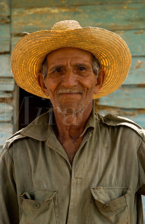 Old farmer man cutting sugar cane in front of old green house near Trinidad Cuba