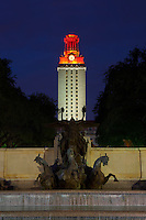 University clock tower illuminated orange after football win with fountain statue.