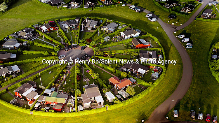 Pictured: The garden city<br /> <br /> Aerial photos show the sun setting on this unique 'garden city', where houses are arranged in circular plots.   The community of Brøndby Haveby - also known as Brøndby Garden City - sits outside Copenhagen in Denmark, and is made up of 284 houses and allotment gardens, where residents can retreat from the chaos of the neighbouring city.<br /> <br /> It developed in 1964 by the late architect Erik Mygind, who believed his design would help increase social interaction among its residents.   He was inspired by the circles in the middle of historic Danish villages where residents would often gather and mingle.   SEE OUR COPY FOR DETAILS<br /> <br /> Please byline: Henry Do/Solent News<br /> <br /> © Henry Do/Solent News & Photo Agency<br /> UK +44 (0) 2380 458800