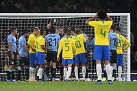 Both teams surround Craig Pawson, after the referee awarded Brazil a penalty during Brazil vs Uruguay, International Friendly Match Football at the Emirates Stadium on 16th November 2018