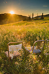 Two chairs with a view through the green summer grass at sundown in the mountains
