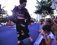 Women in traditional Japanese kimono give gifts to girls at the Pacific Asian Parade in Waikiki, Hawaii