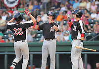 Left fielder Trever Adams (30), left, of the Hickory Crawdads is congratulated after hitting a home run in a game against the Greenville Drive on Sunday, September 2, 2012, at Fluor Field at the West End in Greenville, South Carolina. Hickory won, 8-4. (Tom Priddy/Four Seam Images)