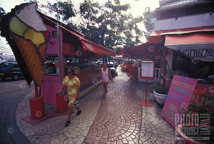 People walking down a street past ice cream vendors and cafes, Papeete, Tahiti