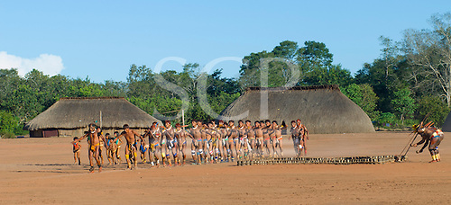 Xingu Indigenous Park, Mato Grosso State, Brazil. Aldeia Waura; a ceremonial dance passing the grave of a recently deceased elder while two cantors chant and shake gourd rattles over the grave.