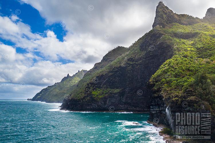 High cliffs and a waterfall on Kaua'i's Na Pali coastline.