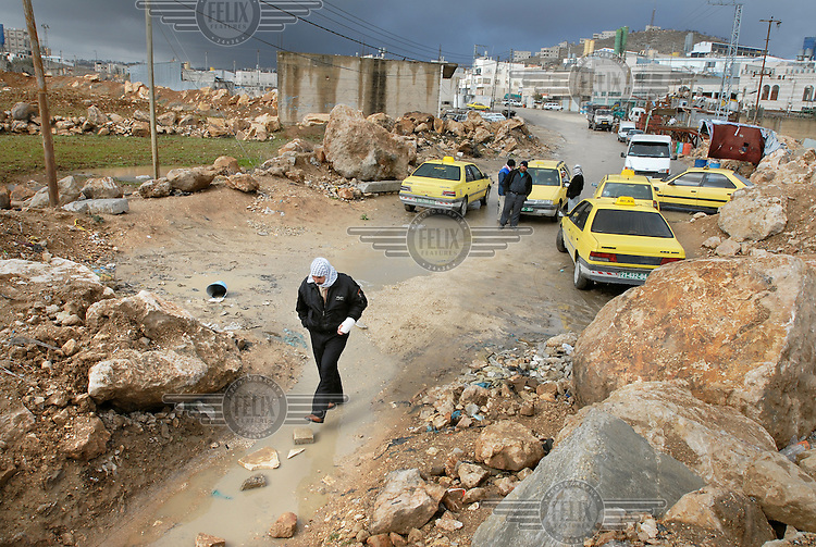 Taxis parked next to an Israeli roadblock in a Palestinian village. The Israeli army has closed most of the roads by blocking them with big stones and cement blocks in order to control movement in the area.