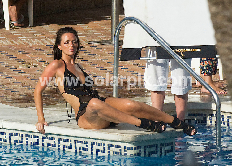 **ALL ROUND EXCLUSIVE PICTURES FROM SOLARPIX.COM**.**WORLDWIDE SYNDICATION RIGHTS**.Hollyoaks actress Jennifer Metcalfe looked stunning as she posed for a calendar shoot by the pool at up market beach club Nikki Beach in Marbella this week. Jennifer, who plays Mercedes in the channel 4 soap was forced to retire to her hotel room half way through the shoot after suffering a bad case of heat stroke brought on by partying at Nikki Beach the day before with her new boyfriend, who she is desperately trying to keep under wraps. The mystery man, who is rumoured to be a property developer, sat in the shade with a towel covering his face for most of the day before the couple were forced to run for the shelter of their room where they remained for the rest of the day..This pic:   Jennifer Metcalfe..JOB REF:  11710    AB1JGS       DATE:   19.07.10.**MUST CREDIT SOLARPIX.COM OR DOUBLE FEE WILL BE CHARGED**.**MUST AGREE FEE BEFORE ONLINE USAGE**.**CALL US ON: +34 952 811 768 or LOW RATE FROM UK 0844 617 7637**