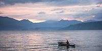 Fisherman in a fishing boat on Lake Toba (Danau Toba) at sunrise, North Sumatra, Indonesia