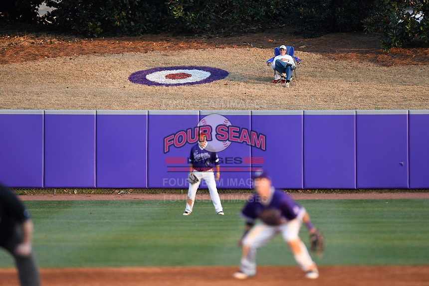 A fan sits next to a large bullseye painted in left field home run territory in game two of a doubleheader between the Furman Paladins and the Harvard Crimson on Friday, March 16, 2018, at Lathan Baseball Stadium on the Furman University campus in Greenville, South Carolina. Furman won, 7-6. (Tom Priddy/Four Seam Images)