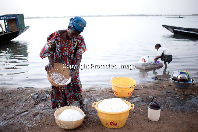 SEGOU, MALI - FEBRUARY 24: A woman cleans rice along the Niger river on February 24 2011, in Segou, Mali. This area of Mali is fertile because of the Niger river and the many dams and channels built to help irrigate for farming. A channel has been built nearby by a Chinese company and it will help Libyan investor to do large scale farming in the area. They have signed a land lease with the government and many farmers has been moved away from their land. Photo by Per-Anders Pettersson..