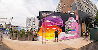 "Buff Monster works on his mural in Bushwick, Brooklyn in New York during the annual Bushwick Collective Block Party on Saturday, June 4, 2016. Music and partying brought some but the real attraction was the new murals  by ""graffiti"" artists that decorate the walls of the buildings that the collective uses.  (© Richard B. Levine)"