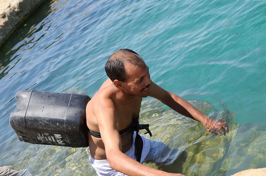 An Egyptian man with a makeshift life preserver at Abu Shuruf Spring