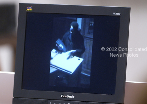 A surveilence video showing Sniper suspect John Allen Muhammad at the hostess stand at a resturaunt in Maryland is displayed on a screen in courtroom 10 at the Virginia Beach Circuit Court in Virginia Beach, Virginia on November 3, 2003. <br /> Credit: Lawrence Jackson - Pool via CNP