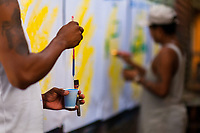 """A Colombian sign painter prepares his brush before writing letters on music party posters in the sign painting workshop in Cartagena, Colombia, 11 December 2017. Hidden in the dark, narrow alleys of Bazurto market, a group of dozen young men gathered around José Corredor (""""Runner""""), the master painter, produce every day hundreds of hand-painted posters. Although the vast majority of the production is designed for a cheap visual promotion of popular Champeta music parties, held every weekend around the city, Runner and his apprentices also create other graphic design artworks, based on brush lettering technique. Using simple brushes and bright paints, the artisanal workshop keeps the traditional sign painting art alive."""