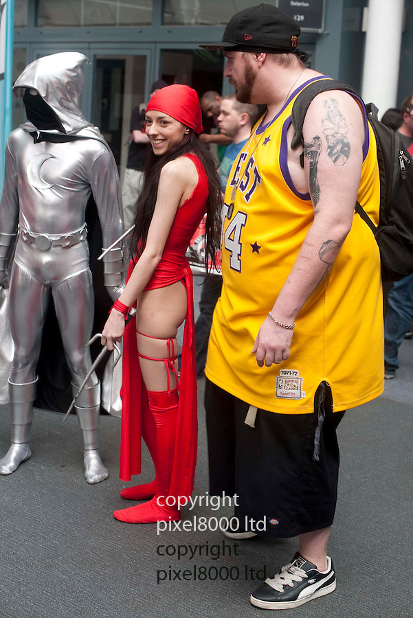 Kapow Comic convention in London today 9.4.11.People dressed as various character from comics and sci fi films attend the convention ..Large fan gets his photo taken with Kira the Assasin.....pic by Gavin Rodgers/ Pixel 8000.07917221968