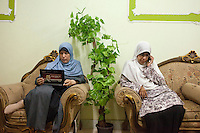 Egypt / Al-Saf / 13.6.2012 / Two Muslim sisters, Dr Omaima Kamel (left) and Dr Heba Hassan (right) , rest before lunch at a meeting with women in the rural village of Al Saf, in the South of Cairo. Dr Omaima's laptop is covered with a campaign sticker for Dr Mohamed Morsi, chairman and Presidential candidate for the Freedom and Justice Party, a political party founded by the Muslim Brotherhood. Al Saf village, Egypt. June 13th, 2012<br /> <br /> © Giulia Marchi
