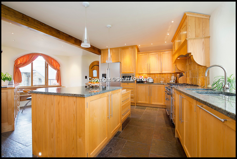 BNPS.co.uk (01202 558833)<br /> Pic: Strutt&amp;Parker/BNPS<br /> <br /> ***Please use full byline***<br /> <br /> The kitchen.<br /> <br /> A stunning country pad that looks like it could have been designed by Hobbit hero Bilbo Baggins has gone on the market for one million pounds.<br /> <br /> The wonderfully wacky house appears to blend in with its surroundings, just like the Lord of the Rings character's humble Hobbit hole.<br /> <br /> The plush five-bedroom property is nestled deep in the rolling hills of Wales' Snowdonia National Park - although it would not look out of place in Middle Earth.<br /> <br /> The house is called Cynefin, meaning 'a sense of place' in Welsh, and is in the tiny village of Llanegryn in Gwynedd wih unrivalled views over the Dysynni Valley.<br /> <br /> It is on the market through estate agents Strutt and Parker for &pound;985,000.