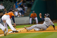 Detroit Tigers second baseman Omar Infante (4) slides into third base ahead of the tag by Astros third baseman Matt Dominguez (30) during the fifth inning of the MLB baseball game against the Houston Astros on May 3, 2013 at Minute Maid Park in Houston, Texas. Detroit defeated Houston 4-3. (Andrew Woolley/Four Seam Images).