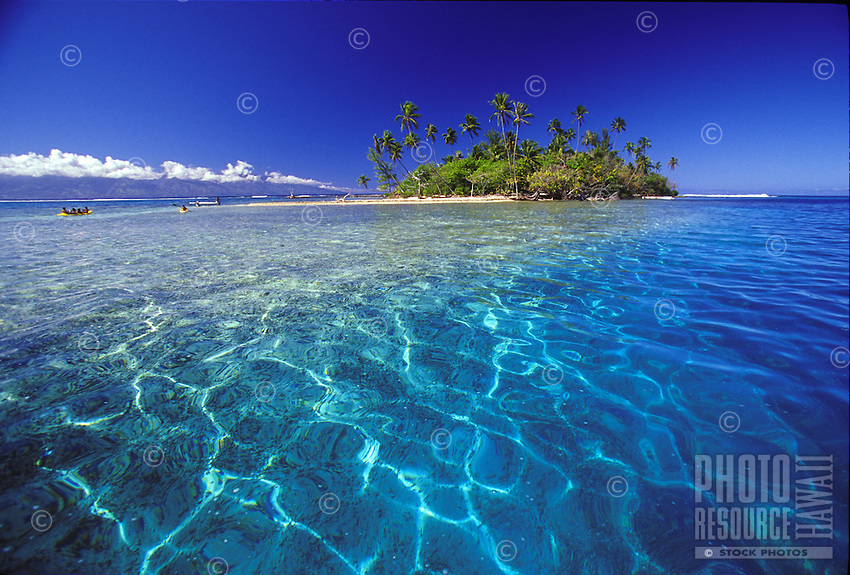 Crystal blue waters of Tahitian lagoon with atol islet in background