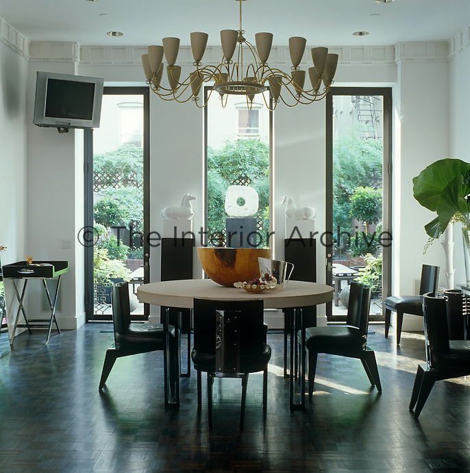 Three long windows look out onto the garden from the dining room of a house in New York whilst a large chandelier by Tommy Parzinger hovers above the table